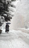 Full winter. Old lady walking i heavy snow Royalty Free Stock Photos