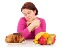 Full woman thinks to eat chicken or fruit. Isolated on white background Stock Photos