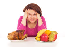 Full woman thinks to eat chicken or fruit. Isolated on white background Stock Photography