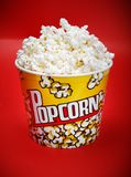 Full yellow bucket of popcorn on red background Royalty Free Stock Image