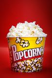 Full yellow bucket of popcorn on red background Stock Images