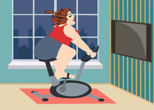 Full young girl is engaged on a stationary bike at home Royalty Free Stock Images
