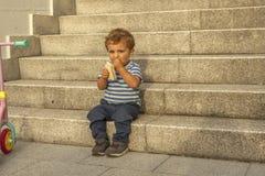 Fulla den gulliga skottståenden behandla som ett barn pojken som har ett mellanmål, sitter i stensta Fotografering för Bildbyråer
