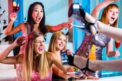 Fulla flickor med utsmyckade coctailar i remsaklubba Arkivfoto