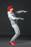 Fullbody portrait of young cool man dancing on dark background. Royalty Free Stock Photos