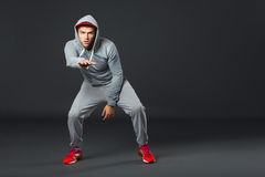 Fullbody portrait of young cool man dancing on dark background. Royalty Free Stock Photo