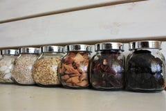 Fulled con tè, i semi ed il vetro secco di frutti conta su precedenti bianchi di legno immagine stock libera da diritti