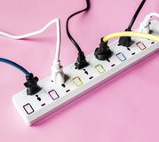 Fulled electrics power supply plug on pink background royalty free stock photos