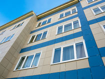Fullföljande av fasaden av det nya lägenhethuset med keramiska tegelplattor royaltyfria bilder