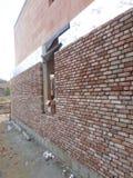 Fullföljande av fasaden av ett privat hus under tegelstenen arkivfoto