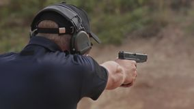 FullHD footage. Man in headphones shoots a pistol on the target. stock video footage