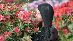FullHD footage of young attractive woman in black leather jacket posing over green exotic background with flowers. FullHD footage of young attractive woman in stock video footage