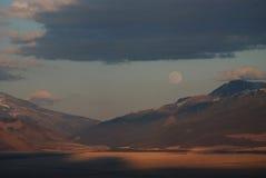 Fullmåne över bergen och solnedgången Arkivbild