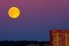Fullmåne över stad Arkivbild