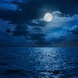 Fullmåne i moln över havet Arkivbilder