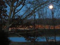 Fullmåne som ställer in över sjön Royaltyfri Foto