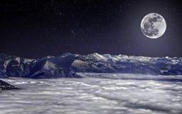 Fullmånen över snöig fjällängar, ovanför moln, under den stjärnklara himlen Arkivfoton