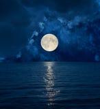 Fullmånen i mörker fördunklar över havet Arkivbild