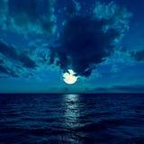 Fullmåne i dramatisk himmel över vatten Arkivfoton