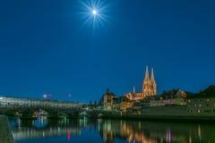 Fullmånenatt i Regensburg Bayern med sikt till kupolen St Peter, stenbron och flodDonauen Arkivfoto