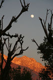 Fullmoon rise  and vivid sunset on snowpeaked   In Stock Photo