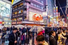 Fullsatt folk som går i den färgrika natten som regnar gatan i den Dotonbori storgatan Arkivbild
