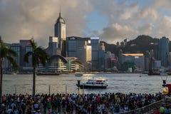 Fullsatt folk som väntar fyrverkeri för nationell dag i regn på strand av Victoria Harbour av Hong Kong Royaltyfria Foton