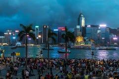 Fullsatt folk som väntar fyrverkeri för nationell dag i regn på strand av Victoria Harbour av Hong Kong Royaltyfri Bild
