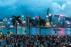 Fullsatt folk som väntar fyrverkeri för nationell dag i regn på strand av Victoria Harbour av Hong Kong Fotografering för Bildbyråer