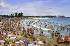 Fullsatt strand och folk i vågorna Royaltyfria Foton
