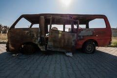 Fullständigt bränd minivan som överges på sidan av en gata Arkivbilder