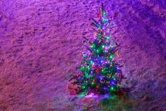 Fullständigt dekorerad upplyst julgran med prydnader på snöig prydliga filialer Royaltyfri Fotografi