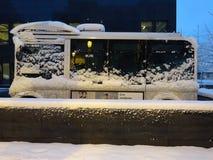 Fullständigt elektrisk minibuss som täckas i snö Arkivbild