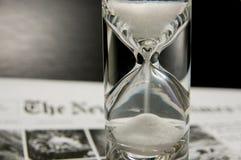 Fullständigt fyllda sandglass på tidningen Arkivfoton