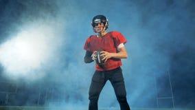 Fullständigt-utrustad manlig amerikansk fotbollsspelare i moln av rök arkivfilmer