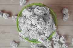 Fullt avfallfack och skrynkligt papper på golv royaltyfri bild