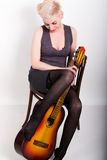 Fullt blont kvinnasammanträde på en stol, fällda ned strumpor lägger benen på ryggen krama gitarren royaltyfri foto