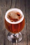 Fullt exponeringsglas av filtrerat ljust öl på en trätabell arkivbild