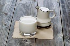 Fullt exponeringsglas av nytt mjölkar och personen som häller på gammalt trä Fotografering för Bildbyråer