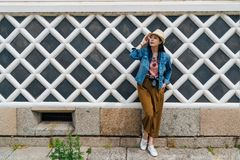 Fullt längdfoto av den unga attraktiva turist- bärande sugrörhatten som litar på den vita netto väggen elegant asiatiskt handelsr royaltyfri bild