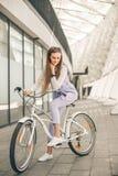 Fullt längdskott av en härlig ung affärskvinna med hennes cykel arkivfoto