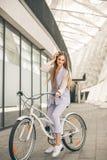 Fullt längdskott av en härlig ung affärskvinna med hennes cykel royaltyfri fotografi