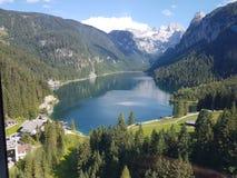 Fullt - sikt av sjön Gosau Österrike som omges av berg arkivfoto