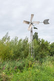 Fully automatic metal wind watermill in a scenic area. Fully automatic metal wind watermill in a nature reserve pumps the water out of a ditch not visible on the Stock Images