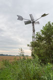 Fully automatic metal wind watermill seen from the back. Backside of a fully automatic metal wind watermill in a Dutch landscape. The mill pumps the water out of Royalty Free Stock Images