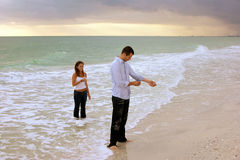 Fully clothed couple standing in ocean at sunset. A surreal image of young couple coming out of the ocean fully dressed at sunset. The man is fixing his shirt Royalty Free Stock Photo
