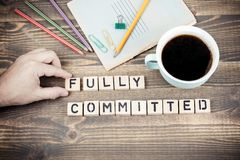 Fully committed. Wooden letters on the office desk royalty free stock images