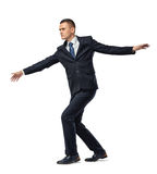 Fully concentrated businessman walking tightrope or border, isolated on white background. Stock Photography