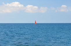 A boat with a red sail floating along the blue sea on a blue sky background royalty free stock images