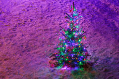 Fully decorated illuminated Christmas tree with ornaments on snowy spruce branches Royalty Free Stock Photography